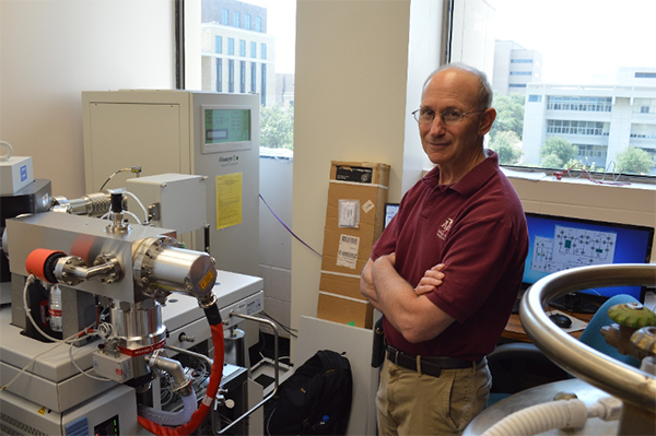 Dr. Grossman with the mass spectrometer used for clumped isotope analyses. (Photo courtesy of Grossman.)