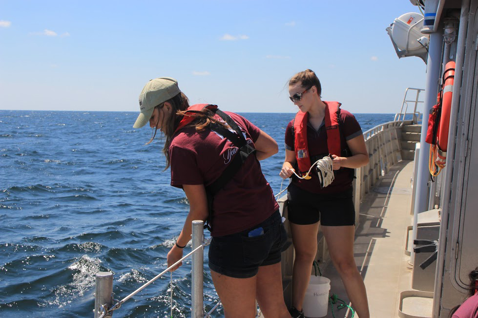Victoria Scriven and a fellow oceanography student doing field work on a cruise. (Photo by Chris Mouchyn, Texas A&M Geosciences)