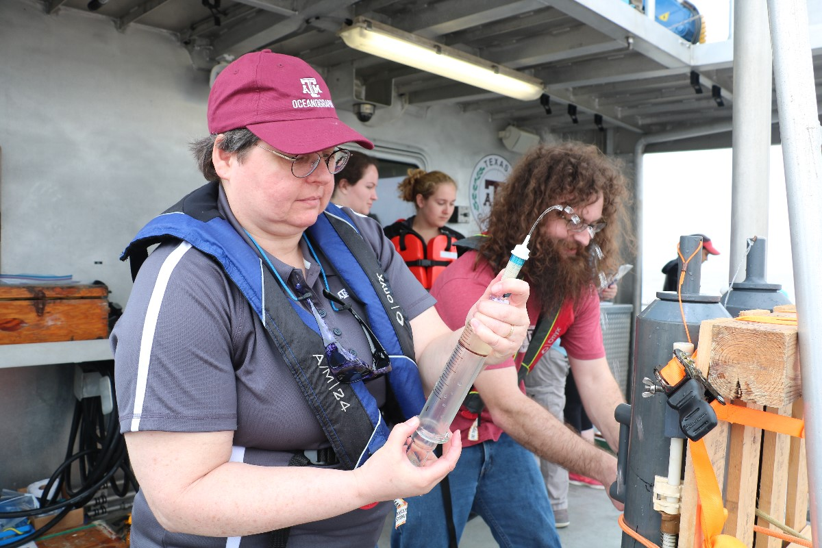 Dr. Shari Von-Lewis (left) and her graduate student, Stanford Goodwin (right) from the Department of Oceanography, collecting seawater sample from Niskin bottle. (Photo by: Bumsoo Kim)