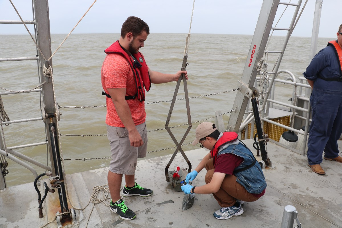 Graduate student, Damian Simonini (left) from the Department of Oceangoraphy, and Jerry Chen (right), from Department of Civil Engineering, collecting sediment sample from grab. (Photo by: Bumsoo Kim)