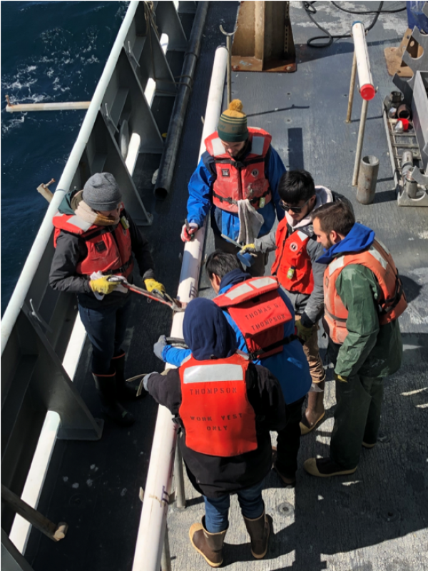 Day watch researchers Jose Córdova, Tanner Eischen, and Ruby Schaufler from Texas A&M University, along Aaron Watters and Mark Yu from Rutgers Universtiy, and Gregorio Diaz Torres from Argentina cutting a sediment core on the deck after recovery. (Photo courtesy of James Wright)