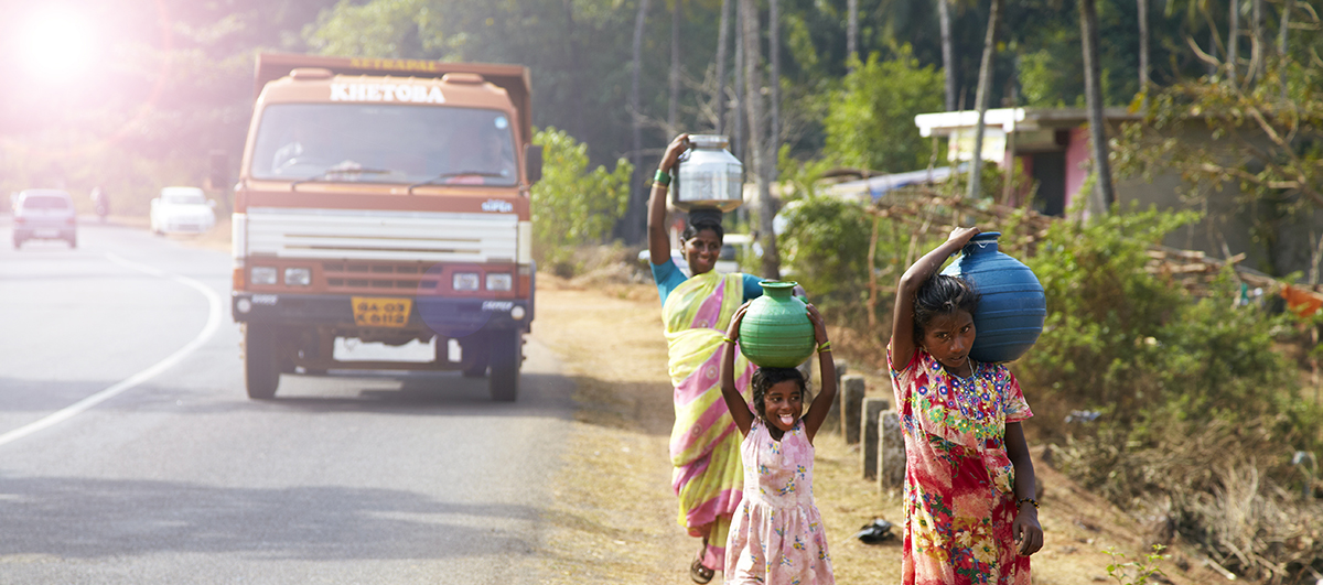 A woman and children carrying water on their heads in traditional pots in rural India. (Photo credit: iStock.)