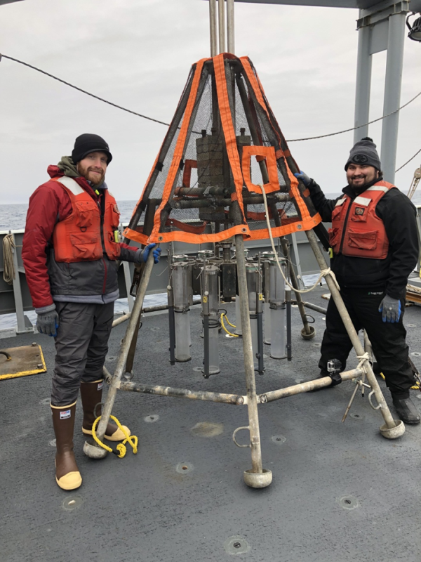 Texas A&M graduate student Richard Rosas (right) and Tim Shamus from Rutgers University (left), standing next to the multi-corer, which has clear plastic tubes attached to it. (Photo courtesy of James Wright.)